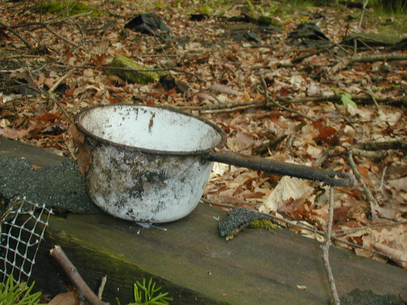 A white metal measuring cup or pot